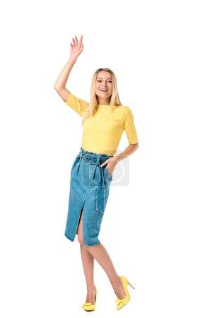 Foto de Mujer joven feliz agitando la mano y sonriendo a cámara aislada en blanco - Imagen libre de derechos