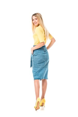 back view of beautiful girl in denim skirt smiling at camera isolated on white