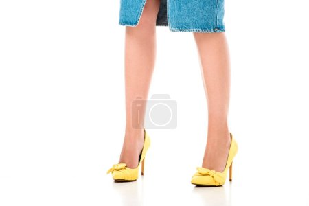 cropped shot of young woman in denim skirt and yellow high heeled shoes standing isolated on white