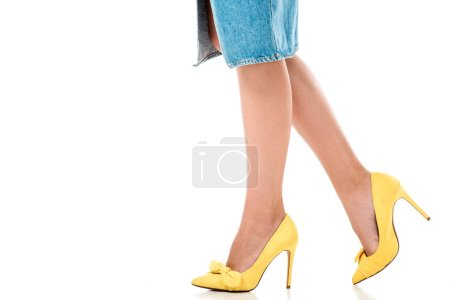 low section of young woman in denim skirt and yellow high heeled shoes walking isolated on white
