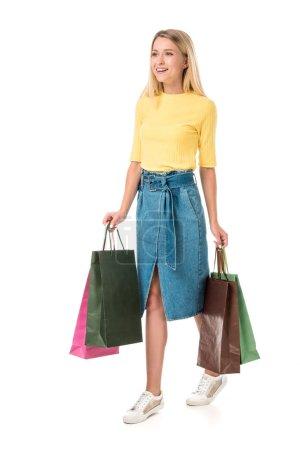 Photo pour Vue pleine longueur de la jeune femme souriante tenant des sacs à provisions et regardant loin isolé sur blanc - image libre de droit