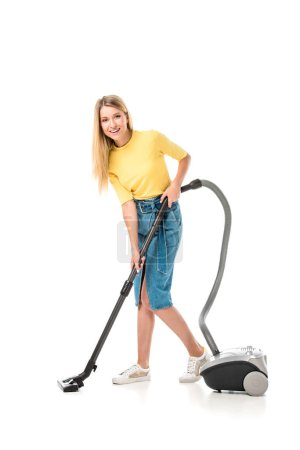 beautiful young woman using vacuum cleaner and smiling at camera isolated on white