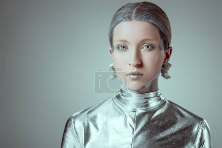 futuristic silver female robot looking at camera isolated on grey, future technology concept