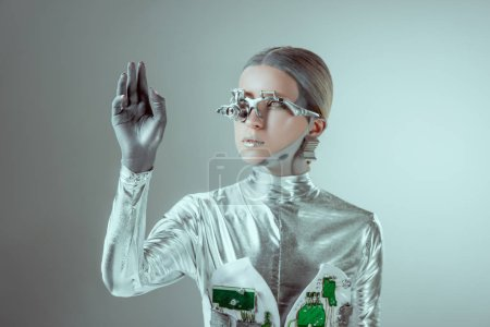 Photo for Futuristic silver robot gesturing with hand and looking away isolated on grey, future technology concept - Royalty Free Image