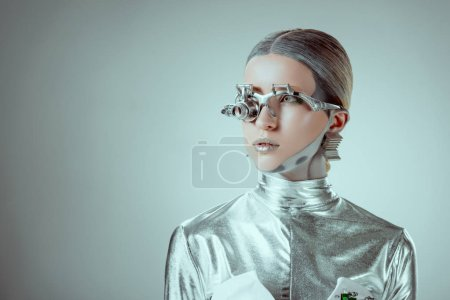 futuristic silver robot looking away isolated on grey, future technology concept