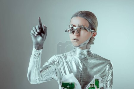 Photo for Futuristic silver cyborg gesturing with hand and looking away isolated on grey, future technology concept - Royalty Free Image