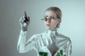 futuristic silver cyborg gesturing with hand and looking away isolated on grey, future technology concept