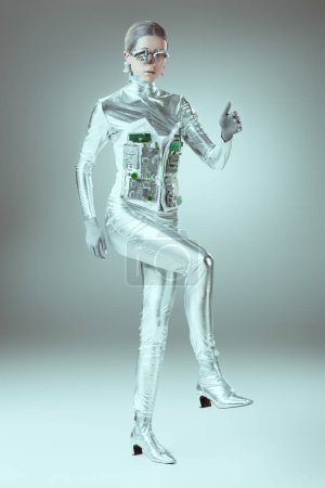 full length view of silver cyborg walking on grey, future technology concept