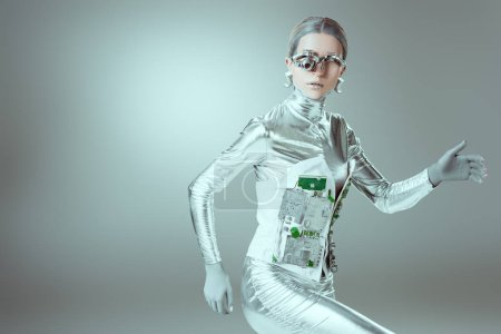Photo for Silver cyborg walking and looking at camera on grey, future technology concept - Royalty Free Image