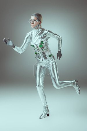 full length view of silver woman robot running on grey, future technology concept