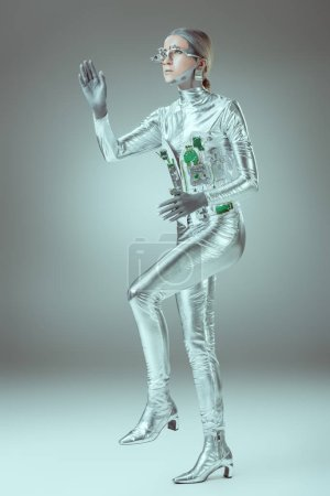 full length view of silver woman robot walking on grey, future technology concept