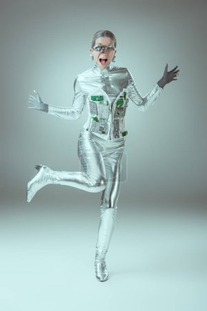 full length view of silver woman robot screaming on grey, future technology concept