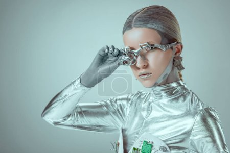 Photo for Futuristic silver cyborg adjusting eye prosthesis and looking at camera isolated on grey, future technology concept - Royalty Free Image