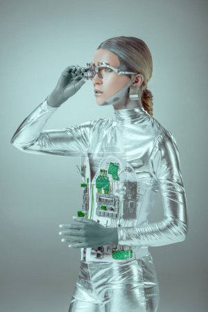 futuristic silver cyborg adjusting eye prosthesis and looking away isolated on grey, future technology concept
