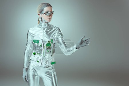 silver woman robot gesturing with hand and looking away on grey, future technology concept