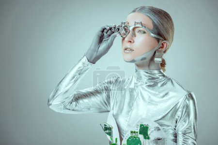 futuristic silver robot adjusting eye prosthesis and looking away isolated on grey, future technology concept