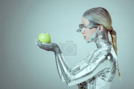 side view of cyborg holding and examining green apple isolated on grey, future technology concept