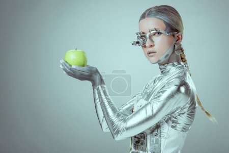 side view of cyborg holding green apple and looking at camera isolated on grey, future technology concept