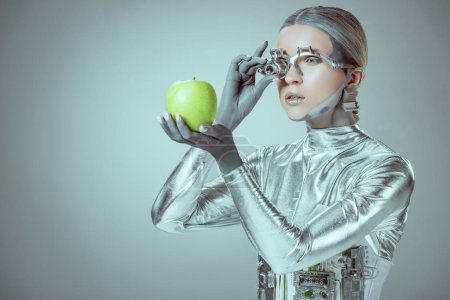 robot examining green apple isolated on grey, future technology concept