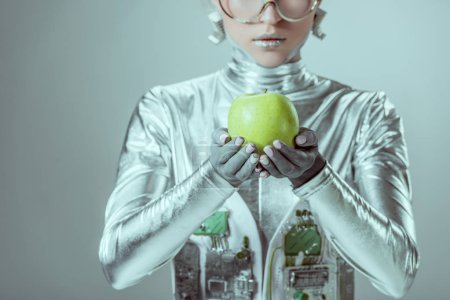 cropped shot of cyborg holding green apple isolated on grey, future technology concept