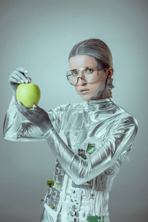 robot in futuristic eyeglasses holding apple and looking at camera isolated on grey, future technology concept