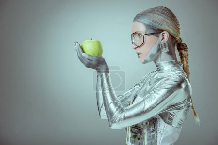 side view of woman robot holding green apple isolated on grey, future technology concept