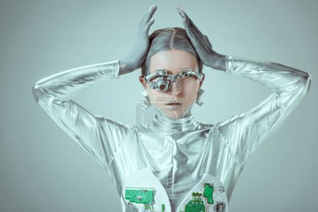 young woman robot touching head and looking at camera isolated on grey, future technology concept