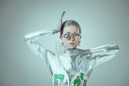 young woman robot looking at camera isolated on grey, future technology concept