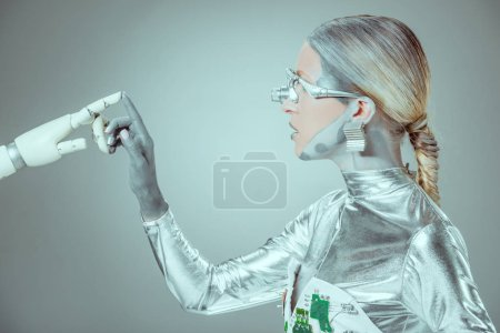 side view of cyborg touching robotic arm isolated on grey, future technology concept