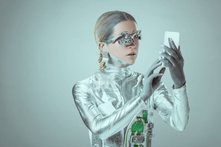 silver cyborg using smartphone isolated on grey, future technology concept