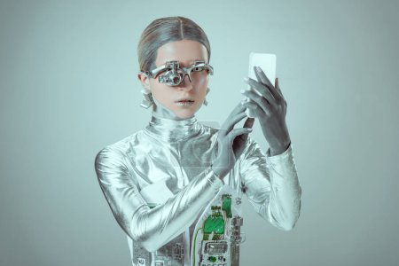 Photo for Young woman robot using smartphone isolated on grey, future technology concept - Royalty Free Image