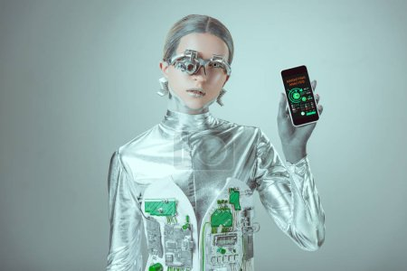 robot holding smartphone with marketing analysis application and looking at camera isolated on grey, future technology concept