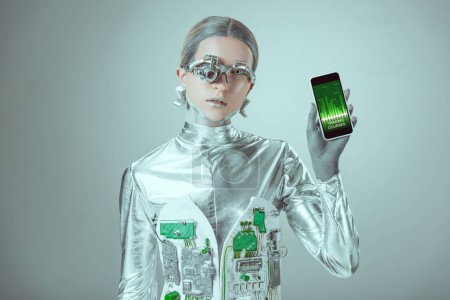 robot holding smartphone with trading courses application and looking at camera isolated on grey, future technology concept
