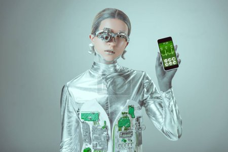 robot holding smartphone with healthcare application and looking at camera isolated on grey, future technology concept