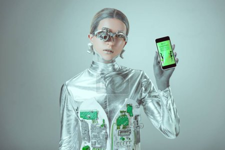 robot holding smartphone with best shopping application and looking at camera isolated on grey, future technology concept