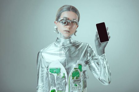 robot holding smartphone with blank screen and looking at camera isolated on grey, future technology concept