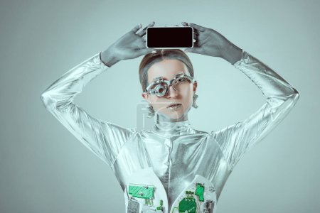 silver robot holding smartphone with blank screen above head isolated on grey, future technology concept