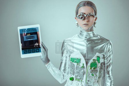 silver robot holding tablet with booking appliance isolated on grey, future technology concept