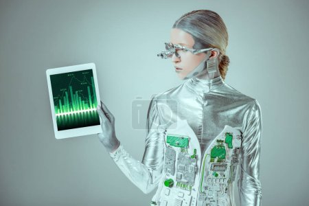 silver robot looking at tablet with chart appliance isolated on grey, future technology concept