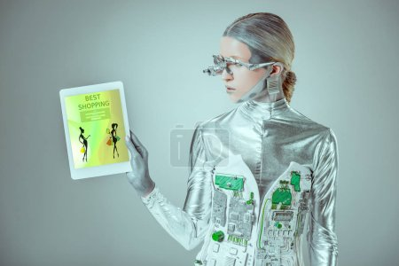 silver robot looking at tablet with best shopping appliance isolated on grey, future technology concept