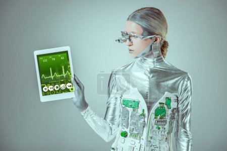 silver robot looking at tablet with medical appliance isolated on grey, future technology concept