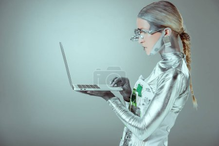 side view of silver robot holding laptop isolated on grey, future technology concept