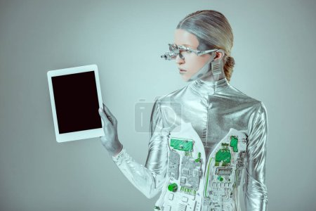 silver robot holding tablet with blank screen isolated on grey, future technology concept