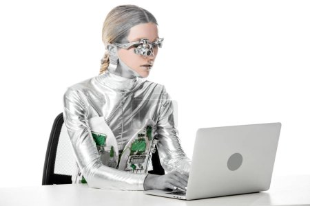 silver robot sitting at table and working with laptop isolated on white, future technology concept