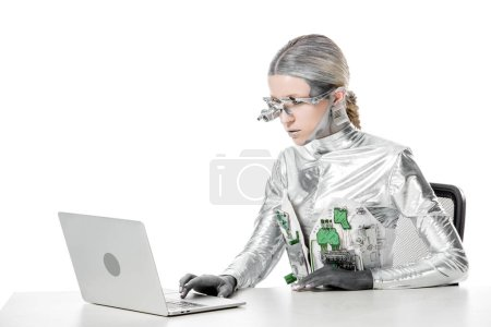 silver robot sitting at table and using laptop isolated on white, future technology concept