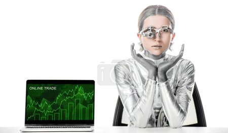 Photo for Silver robot sitting at table near laptop with online trade appliance isolated on white, future technology concept - Royalty Free Image