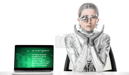 silver robot sitting at table near laptop with medical appliance isolated on white, future technology concept