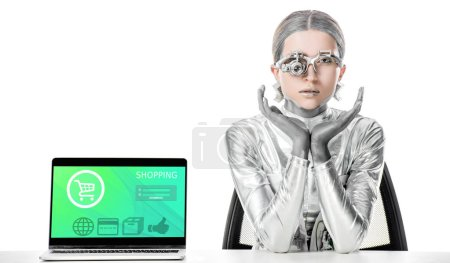 silver robot sitting at table near laptop with shopping appliance isolated on white, future technology concept
