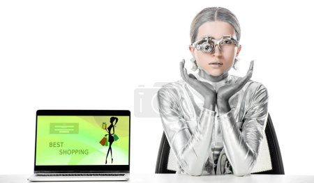 Photo for Silver robot sitting at table near laptop with best shopping appliance isolated on white, future technology concept - Royalty Free Image