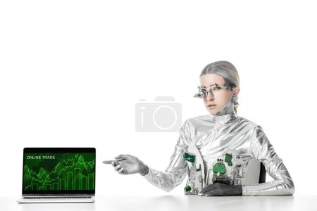 silver robot sitting at table and pointing on laptop with online trade appliance isolated on white, future technology concept